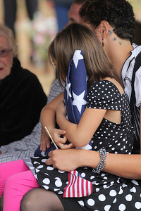 Anyca Miller, the daughter of Staff Sgt. Chris Newman, clutches the flag she was presented during the military funeral for her father in Shelby, NC on November 9, 2011.