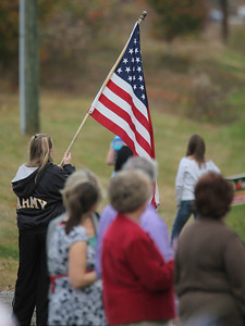 Lea Parsons waves her American flag in honor of Staff SGT Chris Newman.