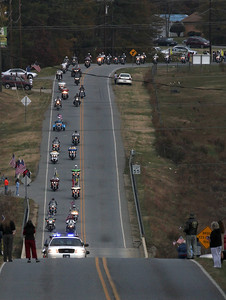 The first police car makes its way up the hill as the start of the precession for Staff SGT Chris Newman