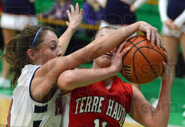 Tribune-Star/Jim Avelis<br /> High pressure: Terre Haute North's Morgan Seeley stuffs South's Kayla Ennen's shot attempt in second quarter action Saturday night.
