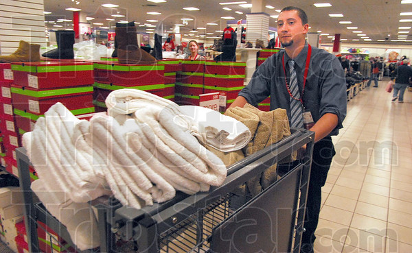 Man in motion: JC Penny's sales associate Will Gardner pushes a cart of towels to be placed on shelves in preparation for coming sales events.