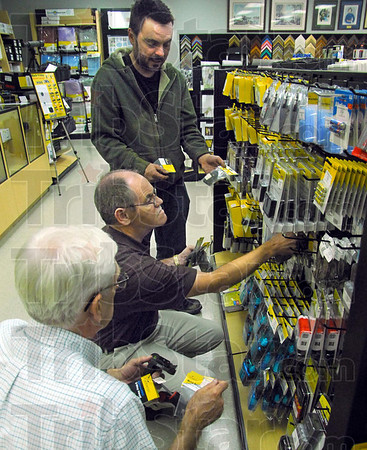 New location: Ray Klotz and Chuck Galloway stock items in their new store location behind Honey Creek Mall in preparation of Black Friday shoppers. Customer Chris Backfish (standing) asks about a sale item.
