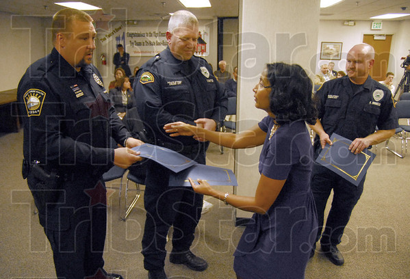 Security awards: School Board president Alpa Patel presents awards to police officers Kris Froschauer, Dave Rafter and Kurt Brinegar during Monday's school board meeting for the capture of a wanted felon at North.