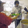 Food prep: Orangie Smith (L) and Fred Whitlock prepare trays at the Bethany House soup kitchen Monday afternoon.