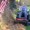 Tribune-Star/Jim Avelis<br /> Leaf patrol: Danny Burke uses his riding mower to solve part of his leaf problem on his Davis Avenue home.
