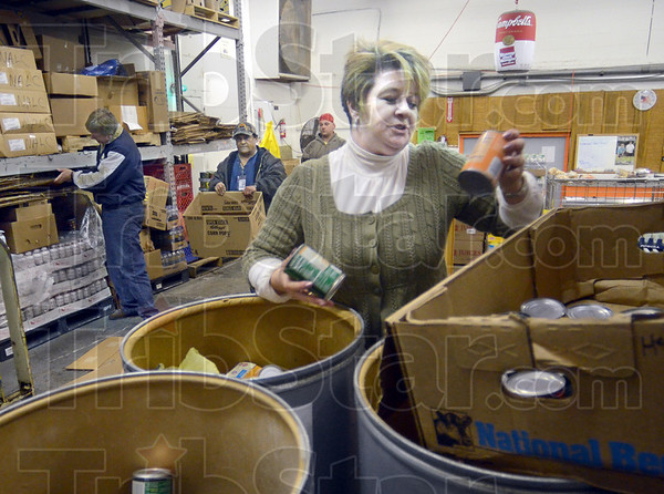 Bank baskets: Catholic Charities Food Bank operations coordinator Lori McKinley prepares food baskets for clients Tuesday afternoon.