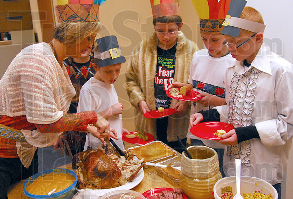 Turkey time: Consolidated fifth grade teacher Teresa Stuckey cuts the turkey for her students during Tuesday's Thanksgiving dinner.