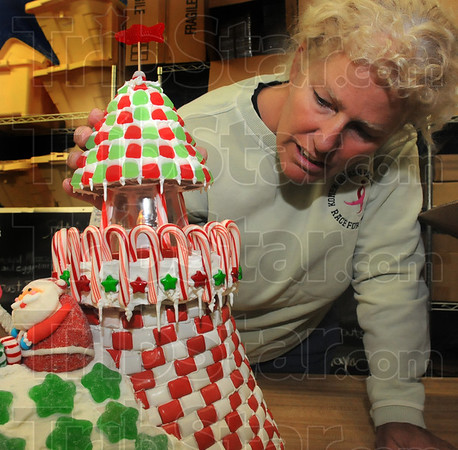 Tribune-Star/Jim Avelis<br /> Candy creation: Boo Lloyd adjusts the cupola of her gingerbread light house before moving it to the Ohio Building Tuesday evening. Her eatery, Crossroads Cafe entered one of many houses in the contest. The event is a fundraiser for the Tribune-Star Christmas Basket Fund, St. Ben's soup kitchen, 14th & Chestnut Community Center and the Salvation Army. Judging and voting starts tonight 7:00p.m. in the Ohio Building. The public is invited.