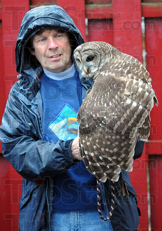 Tribune-Star/Jim Avelis<br /> Maimed: Thibault, a barred owl, is held by John Stokes of SOAR. The raptors and their caregivers stayed overnight with Vigo County school teacher Deborah Walters before presenting their program at Lost Creek and Marshall elementary schools today.