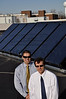 Jim Menart, Ph.D., professor of mechanical and materials engineering (white shirt) and Kyle Hughes, graduate student in the renewable and clean energy program, with the solar collectors atop the WSU student union.
