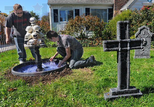 Tribune-Star/Jim Avelis<br /> Good clean fun: Nathan and Carson Lorey clean leaves from the skull fountain in the front yard of their haunted home on South 29th street in Terre Haute.