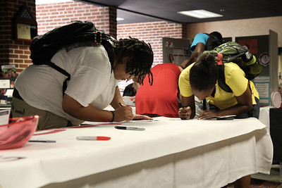 Brittany Blount and Monique Francis sign the Class of 2011 banner.