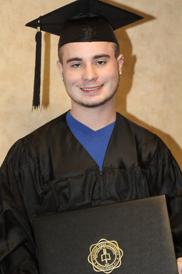 Senior modeling his cap and gown.