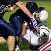 Tribune-Star/Jim Avelis<br /> Coming down: Terre Haute North running back Brother Scank is hauled down by Lawrence North defender Anthony Ledford.