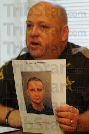 Tribune-Star/Jim Avelis<br /> Booked in: Vigo County sheriff Greg Ewing holds a book-in photo of Joseph L. Williams, suspected of trying to sell radio equipment missing from the Sugar Creek Fire Department.
