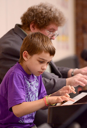 Tribune-Star/Joseph C. Garza<br /> Improv: Deming Elementary fifth-grader Gabe Bennett, 11, plays a pattern of notes as composer Eric Ewazen improvises along with him during Ewazen's presentation Wednesday at the school.