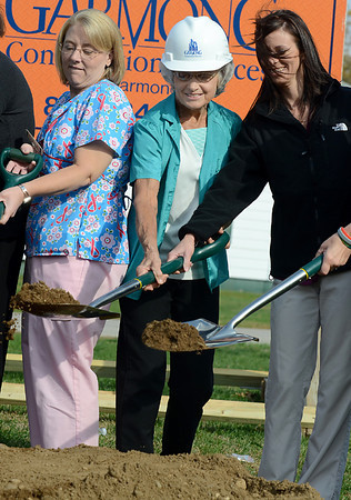 Tribune-Star/Joseph C. Garza<br /> Pitching in: Peggy Lichtenberger, R.N., center, wears a construction hat as she helps turn over dirt with co-workers during the groundbreaking ceremony for the new Cork Medical Center in Marshall, Ill., Wednesday.