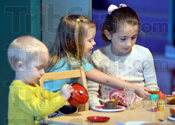 Eat: Evan Hoover, Riley Poynter and Chloe Campbell play with a table setting with make-believe food during their Columbus Day visit to the Children's Museum.
