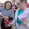 Tribune-Star/Jim Avelis<br /> Passing the torch: Gwen Tucker, CODA Executive Director, lights the candle of Indiana State University sophomore Brooke Griffey at the vigil held for victims of domestic violence.