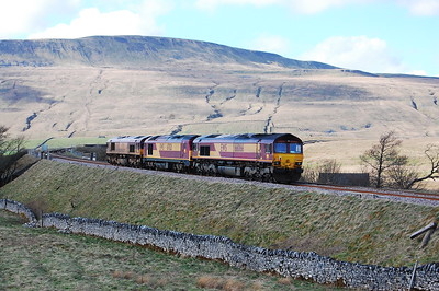 A convoy of EWS-;iveried locomotives comprising 66085, 67021 and 66066 are about to cross Ribblehead Viaduct whilst en route towards Carlisle (02/04/2011)