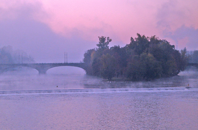 Legii Bridge and its island viewed from Charles Bridge at dawn, with mist rising from the freezing waters.