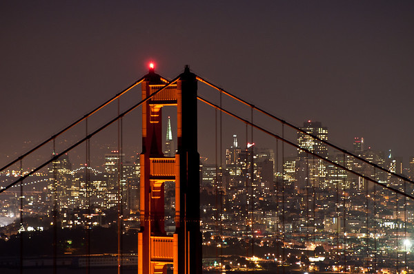 """My friend that I've been shooting a lot with lately had taken some pictures of sunset at the Golden Gate Bridge in which he """"Threaded the Needle"""" -- using the right angle from the Golden Gate Bridge you can position the Transamerica building to be right in the center of one of the towers! There's room for 2 photographers at once. It was pretty windy so I had to bump my ISO up to get the shot, although this one was taken when the wind had stopped and I was able to get a little longer shutter. I want to come back here during Christmas time, when the Transamerica building has a light on the top (a star light) and when it's sunset and not the-sun-is-already-down."""