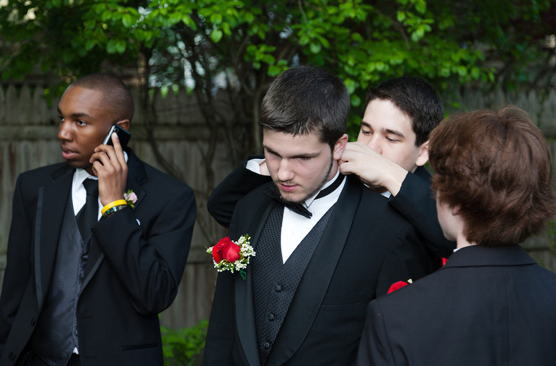 Eli on cellphone, Sergio fixing Liam's bowtie, Connor looking on