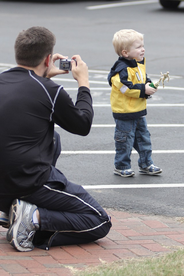 After his mother receives a trophy, a young boy gets his photograph taken.