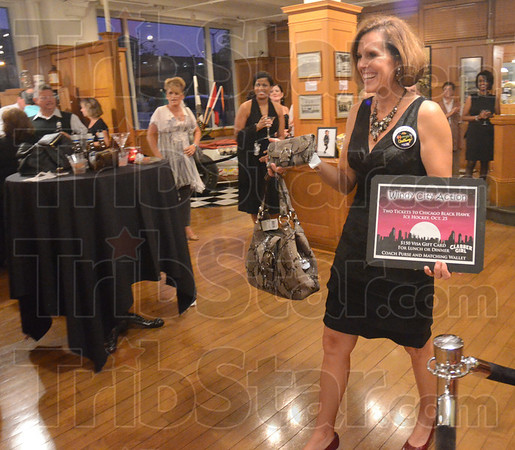 Tribune-Star/Jim Avelis<br /> Looking for bids: Lori Danielson displays the Windy City Package, a Coach purse and tickets to see the Chicago Blackhawks. Money from the auctioned items, won by Casey Schroeppel, went to this year's United Way campaign.