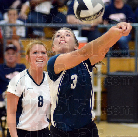 Tribune-Star/Jim Avelis<br /> Support: Terre Haute North's Maddie Howes bumps the ball to a teammate while libero Niki Sneddon watches.
