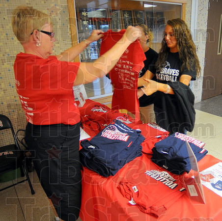 Tribune-Star/Jim Avelis<br /> Just right: Linda Ferguson, grandmother of Terre Haute South volleyball player Maddie Callahan, sells a fundraiser shirt to Kelsey Miller before the Volleyball For The Small game Thursday night. Behind Miller is her mother Jamie Akers.