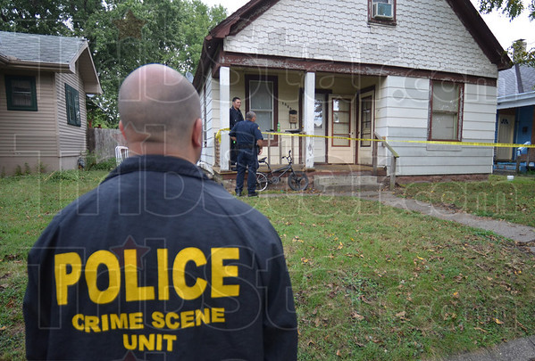 Crime scene: Crime scene detective Gary Shook surveys the scene of Thursday's shooting at 1820 South 8th Street.