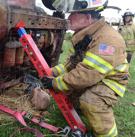 Tribune-Star/Rachel Keyes<br /> To save a life: Fire fighter Larry Akers works with a team of local firefighters to remove a victim trapped under a tractor as part of a Purdue-led Farm Accident Rescue Training event.
