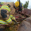 Tribune-Star/Rachel Keyes<br /> Sparks fly: Fire fighter Mike Pruitt cuts into a piece of farm equipment as part of a Purdue-led Farm Accident Rescue Training event at the Vigo County fair grounds.
