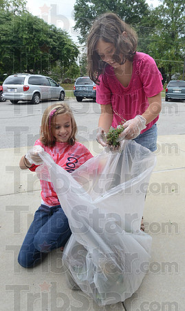 Tribune-Star/Jim Avelis<br /> In the bag: Hannah Davidson and Makayla Price tag team weeds at Sugar Creek Consolidated Elementary School as part of their service project Friday afternoon.