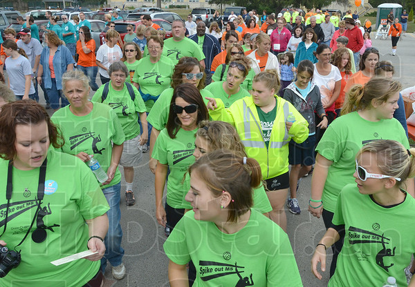 Walkers: A wave of green-shirted walkers passes the starting line for the MS Walk at St. Mary's Saturday morning.