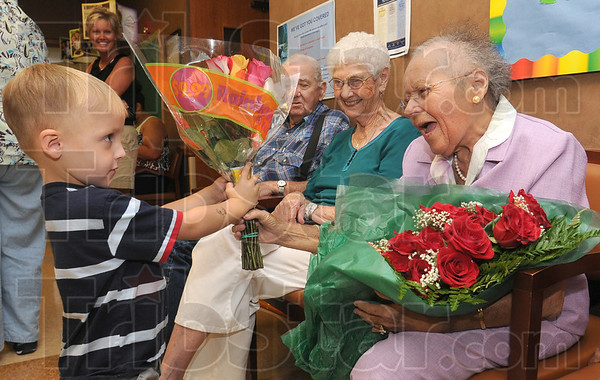 Tribune-Star/Jim Avelis<br /> For you: Wyatt Epling, a neighbor of LaDonna Unger's, hands her a bouquet of flowers at a reception held for her and other long time dialysis patients.