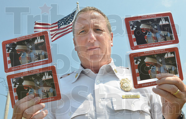 Framed: Terre Haute Fire Chief Jeff Fisher holds four of the 50 frames that will be on display at City Hall honoring firefighters killed on 911.