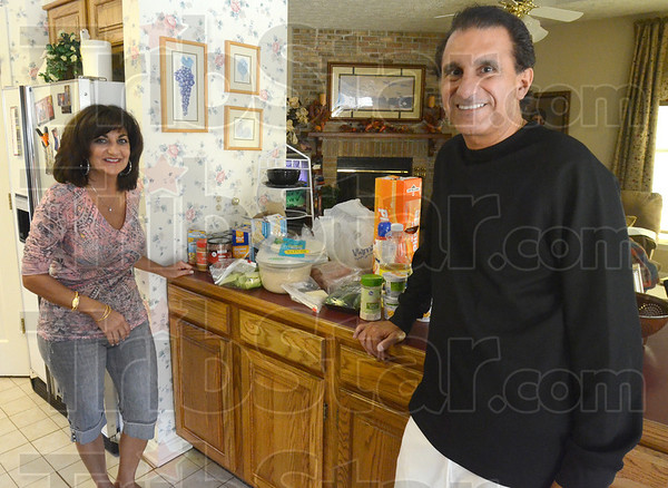Tribune-Star/Jim Avelis<br /> One week: Claudia and Dan Tanoos stand by the remainder of their weeks' worth of food Wednesday evening. Very little meat was on their grocery list, with rice and pasta making up a good deal of menu.