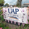 Pink project: UAP employees Sarah Marts (L) and Susan Snider decorate their sign Wednesday afternoon. The race route goes right past the UAP Clinic.