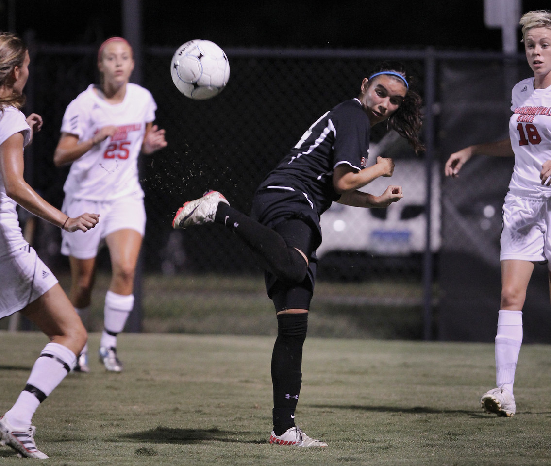 Karyn Latorre (14), though surrounded by opposing players, kicks the ball away to a teammate.