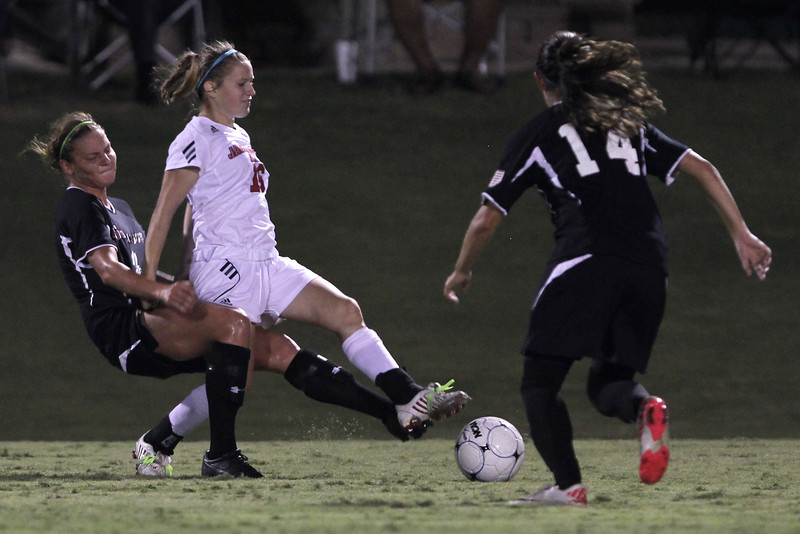 Megan Reimer (4) struggles with a Jacksonville State player to regain possession of the ball, while Karyn Latorre (14) awaits her chance to step in.