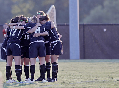 The women's soccer team's starting players huddle before their game against Jacksonville State begins.
