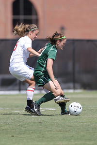 Tina Frost (6) sneaks her foot in between an opposing player's legs to steal the ball away.