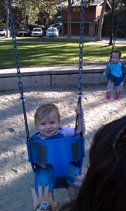 Abby pushes Shai on the swings