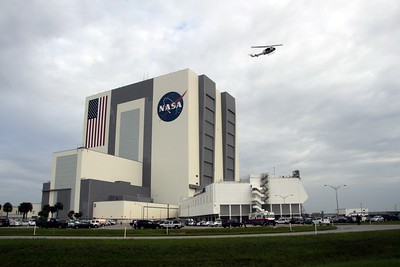 A NASA Emergency Response Team helicopter flies past the Vehicle Assembly Building just prior to crew loading