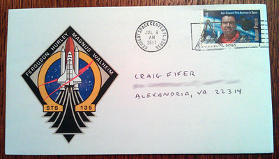 A commemorative event cover featuring a cachet of the STS-135 mission insignia, and bearing a pictorial cancellation by a postal unit at the Kennedy Space Center