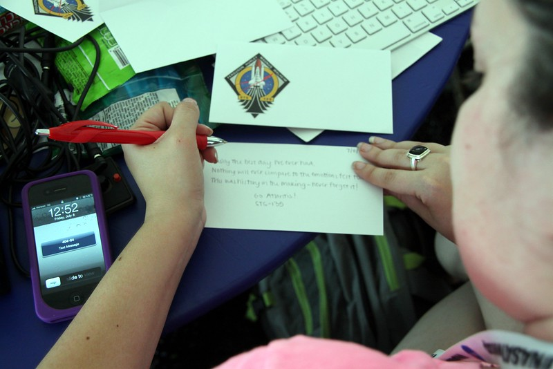 @glancz records a memory of the launch to mail to herself in a commemorative event cover featuring a cachet of the STS-135 mission insignia, to receive a pictorial cancellation by a postal unit at the Kennedy Space Center (photo taken with permission)