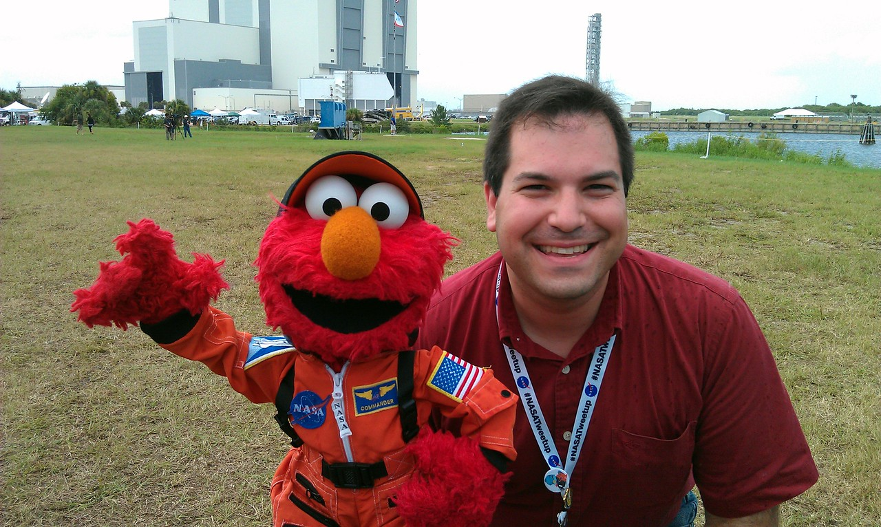 Craig and Elmo at the Press Site, with the Vehicle Assembly Building, Countdown Clock, and Ares 1 mobile launch tower in the background