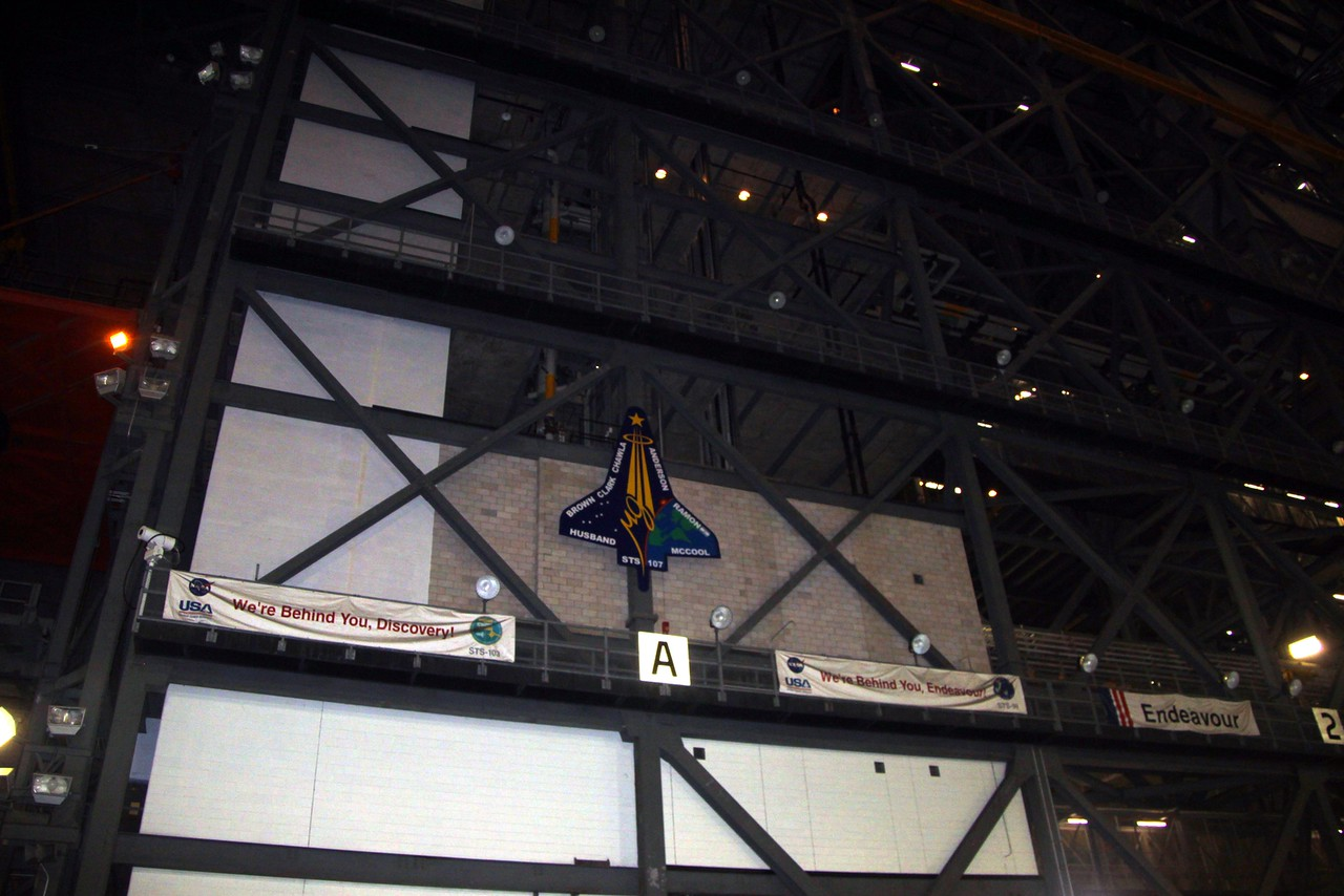 Banners signed by the teams that supported each Space Shuttle mission hang in the Vehicle Assembly Building.  In the center of the photo is the mission patch for STS-107, which ended with the loss of Columbia and her crew.  Behind the cinderblock wall is the final resting place of the debris recovered from the accident.